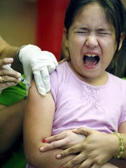 Rachel Denny Clow/Caller-Times Miranda Gonzalez, 9, gets immunizations Feb. 18, 2015 while her mother, Yvette Rodriguez holds her at the Robstown Clinic operated by the Corpus Christi-Nueces County Public Health District.