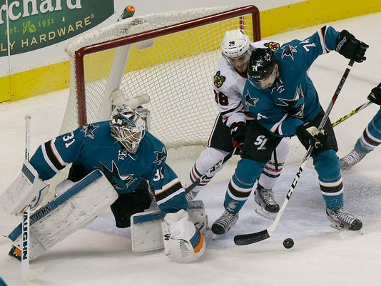 San Jose Sharks goalie Martin Jones (31) blocks the net as defenseman Dylan DeMelo (74) and Chicago Blackhawks right wing Ryan Hartman (38) reach for the puck during the first period of an NHL hockey game in San Jose, Calif., Wednesday, Nov. 23, 2016. (AP Photo/Jeff Chiu)