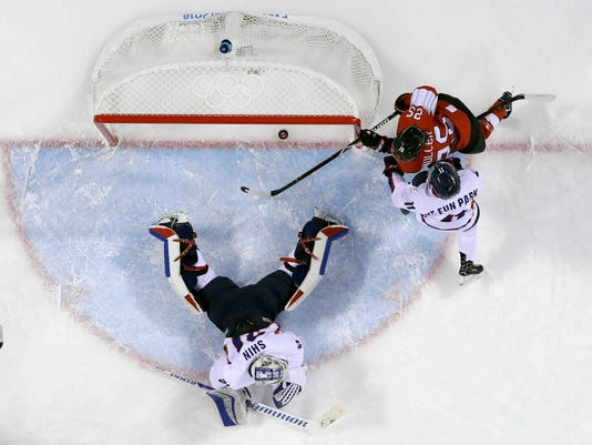 Alina Muller, of Switzerland, scores a goal against =South Korea's goalie Shin So-jung and South Korea's Park Ye-eun, of the combined Koreas team, during the first period of the preliminary round of the women's hockey game at the 2018 Winter Olympics in Gangneung, South Korea, Saturday, Feb. 10, 2018. (AP Photo/Frank Franklin II)