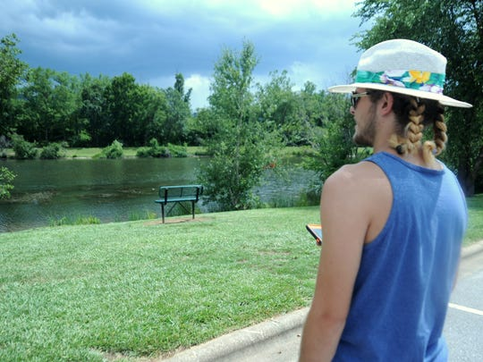Travis Robinette surveys the water in Charles D. Owen Park in an effort to determine where Pokémon may be lurking.