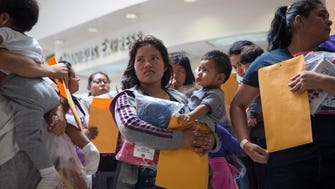 Immigrants wait to head to a nearby Catholic Charities relief center after being dropped off at a bus station shortly after release from detention.