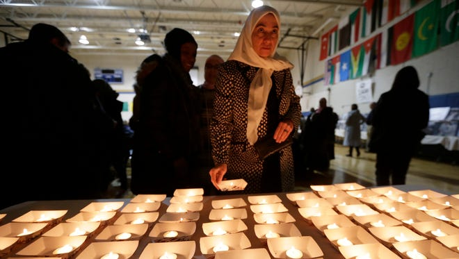 Khuloud Labanieh of Greendale gets a candle during the vigil.