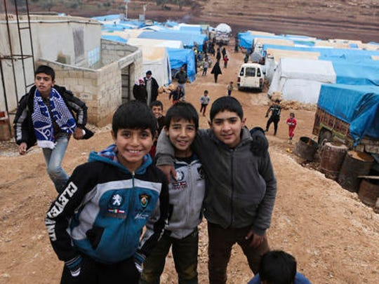 Syrian children, evacuated from Aleppo, smile to photographers in a refugee camp near Idlib, Syria, Friday, Dec. 16, 2016. Turkey's Foreign Minister Mevlut Cavusoglu says 7,500 civilians have been evacuated from the Syrian city of Aleppo and that he has reached out to Tehran in a bid to keep the process on track.