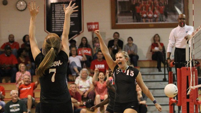 Leon seniors Anna Cay Ford (7) and Caroline Kirk (15) celebrate a point during Tuesday night's home win over Niceville to open the Class 8A playoffs. Ford had 15 assists as the Lions swept the Eagles, and Kirk had 11 kills and four blocks.