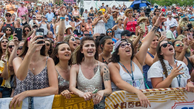 Fans sing along as Luke Combs performs on the Riverfront Stage at the CMA Music Festival in Nashville, Tenn., Sunday, June 11, 2017.
