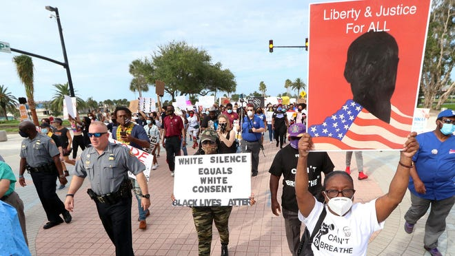 Daytona Beach police chief Craig Capri and other officers join protesters marching from City Island to City Hall, Thursday June 11, 2020 demanding justice and change following the death of George Floyd killed by a police officer in Minneapolis.
