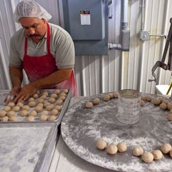 An employee of a small business in Iowa rolls dough balls for making tortillas.