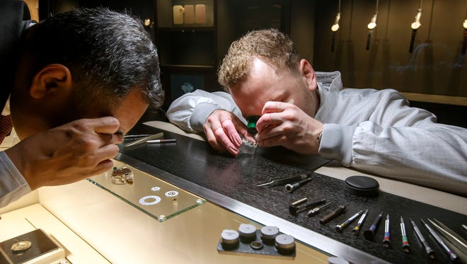 A visitor, left, looks at parts of watches next to a watchmaker at a watchmaking fair in Geneva, Switzerland, on Jan. 15, 2018.