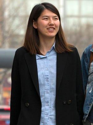 In this April 18, 2015 photo, Chinese activist Li Tingting, walks along a street in suburban Beijing.