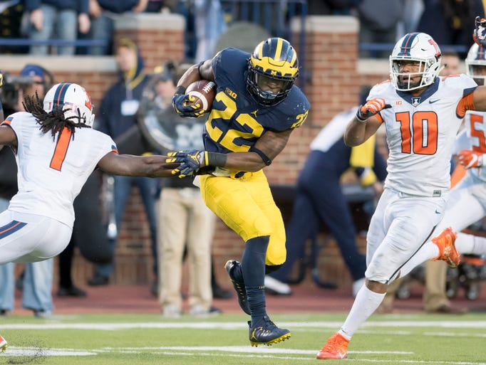 Michigan running back Karan Higdon evades tackles by