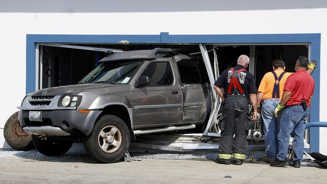 An SUV pokes through a side glass window from the inside of the Freeway Car Wash on Newport in East Providence on Friday afternoon.