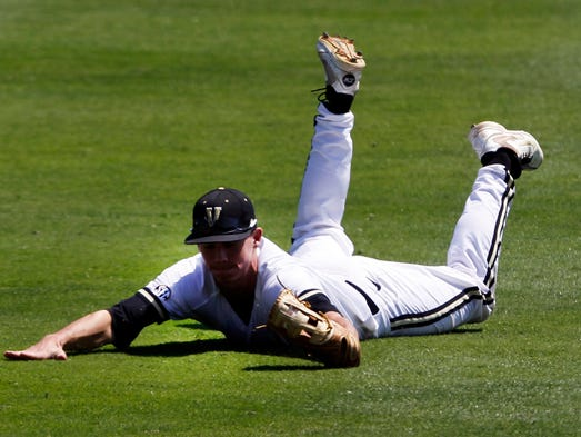 Vanderbilt's Bryan Reynolds dives and catches a fly ball during the fourth inning against Tennessee at the Southeastern Conference NCAA college baseball tournament on Tuesday, May 20, 2014, in Hoover, Ala.