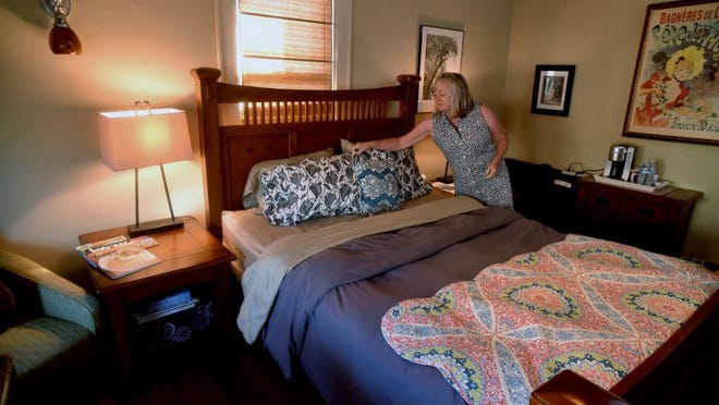 Faith McDaniel makes up one of the beds in the bed-and-breakfast she operates with her husband, Doug, in Knoxville's Fourth and Gill neighborhood Wednesday, Aug. 3, 2016. The city is looking at ordinances that would regulate airbnb rentals, which officials say would protect neighborhoods while still allowing operators to continue their business. It also would likely include requiring airbnb renters to pay hotel/motel tax. The McDaniels welcome clarification in the law.