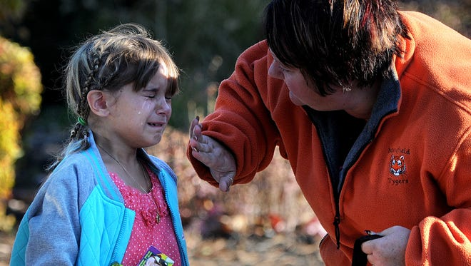 Chloe Harriger, a fourth grader at Malabar Intermediate School, has tears wiped from her face by her mother Penny Harriger after she was evacuated due to another bomb threat Wednesday morning. Jason J. Molyet/News Journal