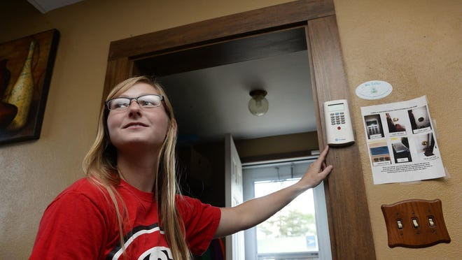 Tricia DeBoer shows the alarm that protects her rental home Aug. 20 on St. Cloud's south side. DeBoer, who will be a St. Cloud State University senior this year, says she feels safer knowing that the home she shares with three roommates has been updated with security features.