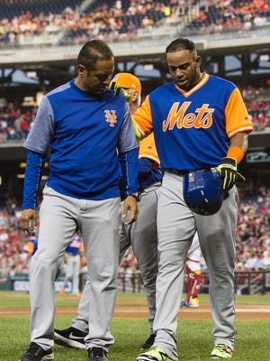 Yoenis Cespedes is helped off the field by Mets head athletic trainer Ray Ramirez.