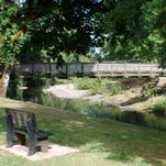 A wooden walking bridge across Rickreall Creek connects the two sides of Dallas City Park.