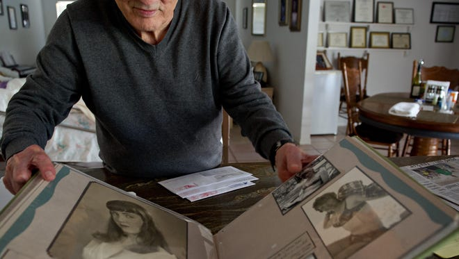 John Consoli shows a photograph Feb. 12, 2015, of his wife, Patricia, in an album filled with photos, letters and other keepsakes devoted to her life and memories. John tends to his wife, who has Alzheimer's disease, at home in Vero Beach with help from home healthcare aides that he said are like part of his family.