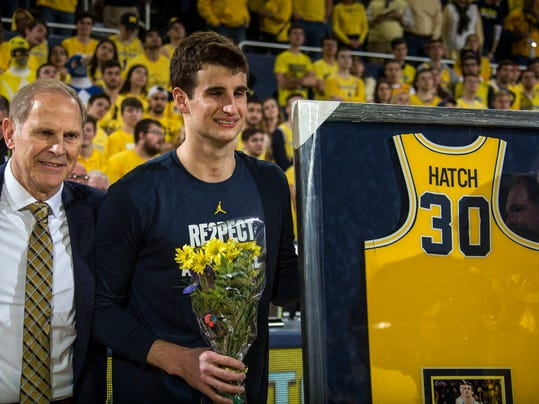 FILE - In this Feb. 18, 2018, file photo, Michigan head coach John Beilein, left, stands with Austin Hatch, center, to honor Hatch's participation with the Michigan basketball team during senior day celebrations prior to an NCAA college basketball game against Ohio State, at Crisler Center in Ann Arbor, Mich. When Michigan's run to the Sweet Sixteen brought Hatch back to downtown LA this week, he was grateful for the chance to see his uncle, his extended family and his Loyola coach, Jamal Adams. They all plan to be in the stands Thursday when Michigan faces Texas A&M, with Hatch helping the Wolverines from his spot on the bench. (AP Photo/Tony Ding, File)