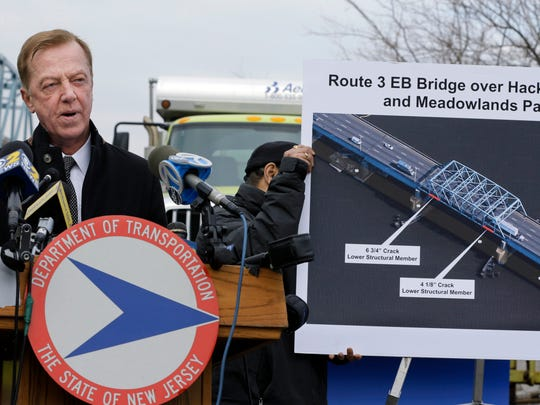 New Jersey State Transportation Commissioner Jamie Fox, center, answers a question about the closure of the right lane of the Route 3 bridge eastbound that leads to the Lincoln Tunnel Thursday, Jan. 22, 2015, at the Department of Transportation maintenance yards in Secaucus, N.J. The right-hand lane on the bridge eastbound was closed Wednesday because of cracks in its support structure. The lane will remain closed until repairs are complete in about two weeks. (AP Photo/Mel Evans)