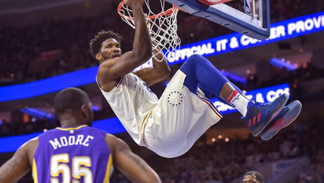 Feb 9, 2018; Philadelphia, PA, USA; Philadelphia 76ers center Joel Embiid (21) hangs on the rim after dunking during the first quarter against the New Orleans Pelicans at the Wells Fargo Center. Mandatory Credit: John Geliebter-USA TODAY Sports