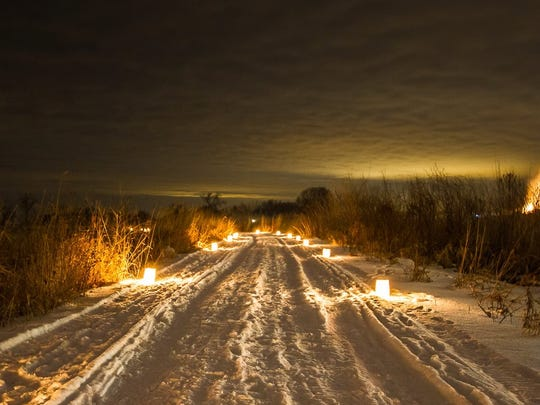 Candles provide light on a snow-covered path at Horicon Marsh.