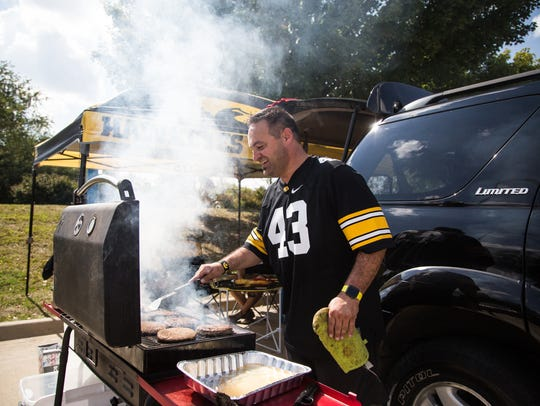 Frank Long cooks burgers at at tailgate near Kinnick