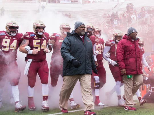 Florida State interim head coach Odell Haggins and the team walk out together at the beginning of the Walk O ns Independence Bowl in Shreveport, Louisiana.