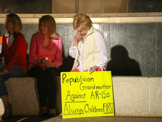 Some of the vigil attendees brought signs to voice their opinion on gun control.