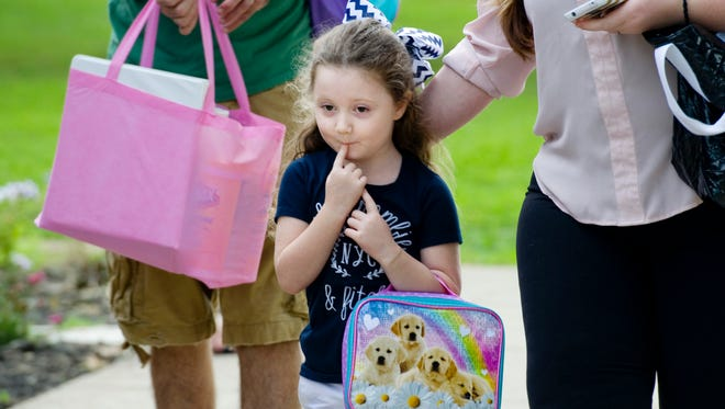 Paityn Hunt, 5, approaches the Oak Hill School mascot, Wildcat, on the first day of school Wednesday morning. The youngster was starting kindergarten.