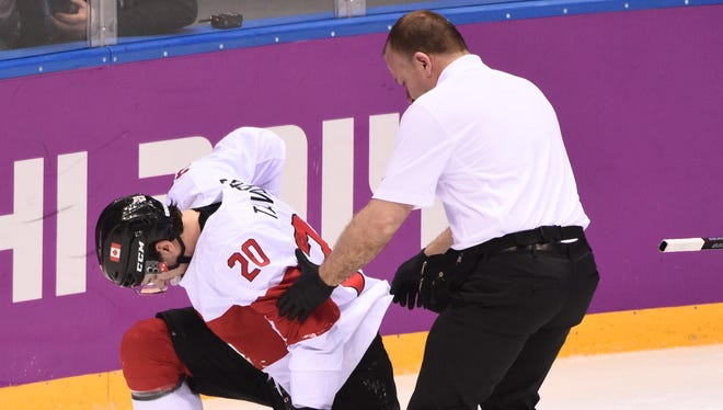 Canada forward Jon Tavares is helped up by a trainer during the men's ice hockey quarterfinals against Latvia.