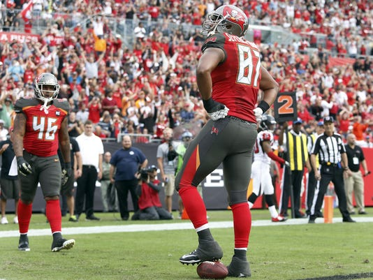 Tampa Bay Buccaneers tight end Austin Seferian-Jenkins (87) stands on the football after catching a one-yard touchdown pass during the fourth quarter of an NFL football game against the Atlanta Falcons, Sunday, Nov. 9, 2014, in Tampa, Fla. Looking on is fullback Jorvorskie Lane (46). (AP Photo/Brian Blanco)