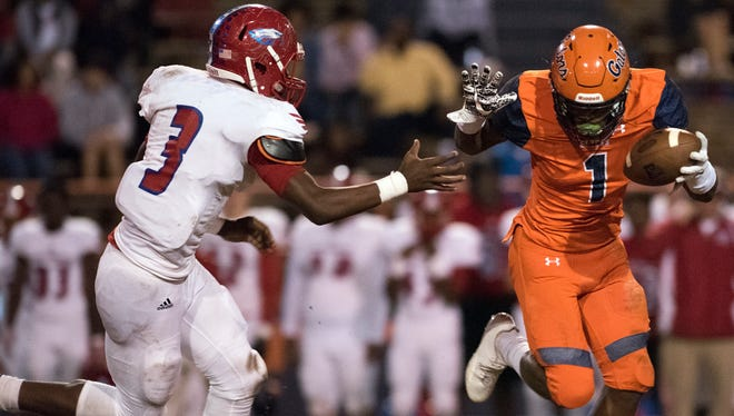 Escambia High School's Jacob Copeland, (No. 1) fights off the attempted tackle of Pine Forest High School's Jaylen Clausell, (No. 3) during Friday night's District 1-6A football playoffs.