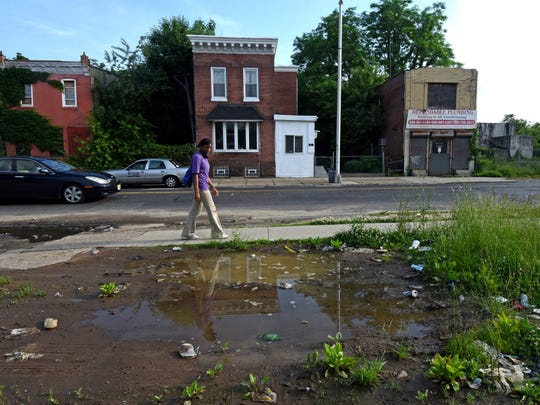 Camden High School junior Kyla Evans passes by puddles on Kaighn Avenue as she walks to school.