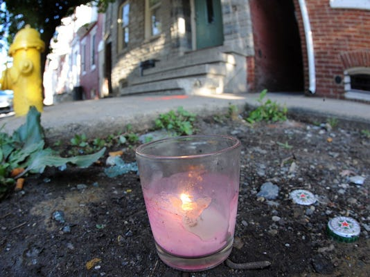 A lit candle sits near where 17-year-old Patrick Winter was shot and killed Saturday, June 14, 2014.
