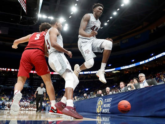 Texas A&M's Robert Williams (44) leaps as he chases a ball out of bounds while teammate Savion Flagg and Alabama's Alex Reese (3) watch during the second half in an NCAA college basketball game at the Southeastern Conference tournament Thursday, March 8, 2018, in St. Louis. Alabama won 71-70. (AP Photo/Jeff Roberson)