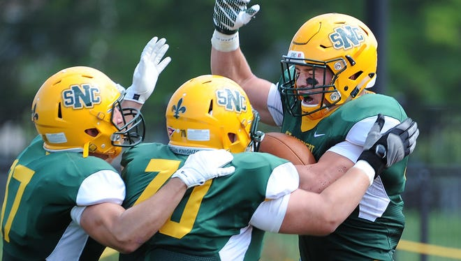 St. Norbert College running back Brad Boockmeier (44), right, celebrates a touchdown with Brock Becker (70) and Brett Olson (17) on Saturday as the Green Knights defeated Carthage College 35-6 at Donald J. Schneider Stadium.