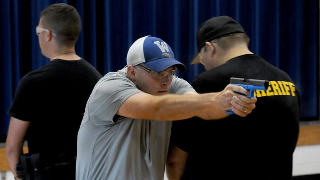 Chris Hulsmeyer of the Bucyrus Polices Department trains on close quarters with a weapon Wednesday morning in the gymnasium at Wynford Elementary School.