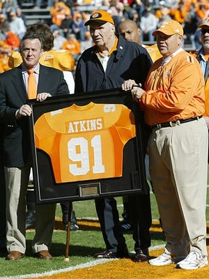 In this Nov. 19, 2005, file photo, Tennessee coach Phillip Fulmer, right, and university president John Petersen, left, assist Doug Atkins with a framed jersey as his No. 91 was retired before Tennessee's NCAA college football game against Vanderbilt in Knoxville, Tenn. Atkins, a defensive lineman who earned induction into both the Pro Football Hall of Fame and College Football Hall of Fame, died Wednesday morning, Dec. 30, 2015, of natural causes at Fort Sanders Regional Medical Center in Knoxville, Tenn. He was 85.