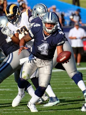 This Saturday, Aug. 13, 2016 photo Dallas Cowboys quarterback Dak Prescott hands off against the Los Angeles Rams in the first half of a preseason NFL football game, in Los Angeles.
