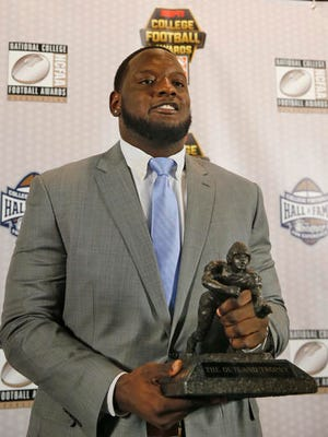 Alabama lineman Cam Robinson holds the Outland Trophy after being named college football's most outstanding interior lineman Thursday.