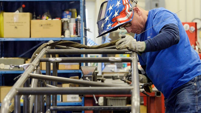 Former sprint car driver Doug Wolfgang works on a new sprint car chassis Thursday at his Wolfweld shop in Tea.