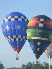 Balloons pilots by Rhett Heartsill, left, and Shawn Raya, bump at Wednesday's first target.