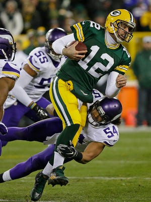 Green Bay Packers quarterback Aaron Rodgers (12) takes a hit during a scramble on a tackle by Minnesota Vikings middle linebacker Eric Kendricks (54) at Lambeau Field.