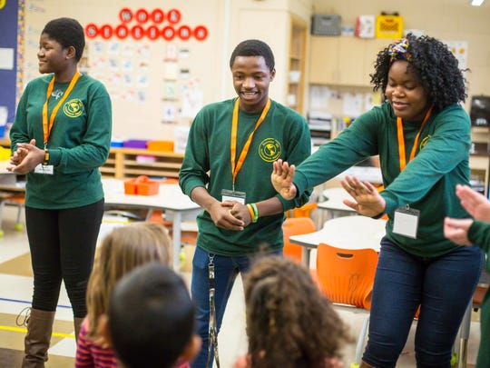 Ferdinand Alobo, center, teaches children at Moore Elementary in Des Moines with the Hoover High School Difference Makers Monday, Nov. 20, 2017. 