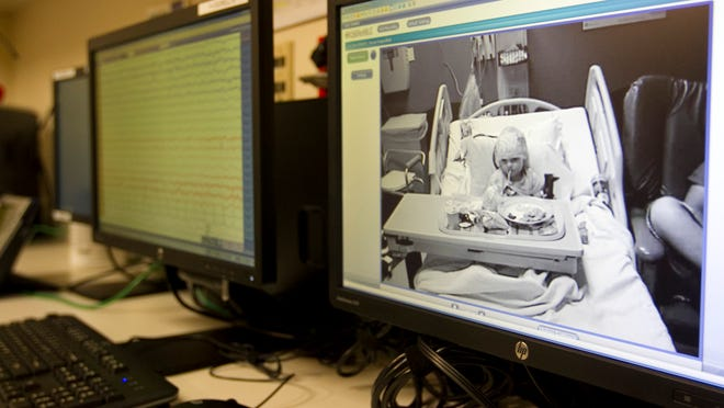 An EEG technician monitors Logan Mendres for seizures over a 24-hour period at HealthPark Medical Center. The monitor on the left shows his brain activity and on the right is live video of his room.