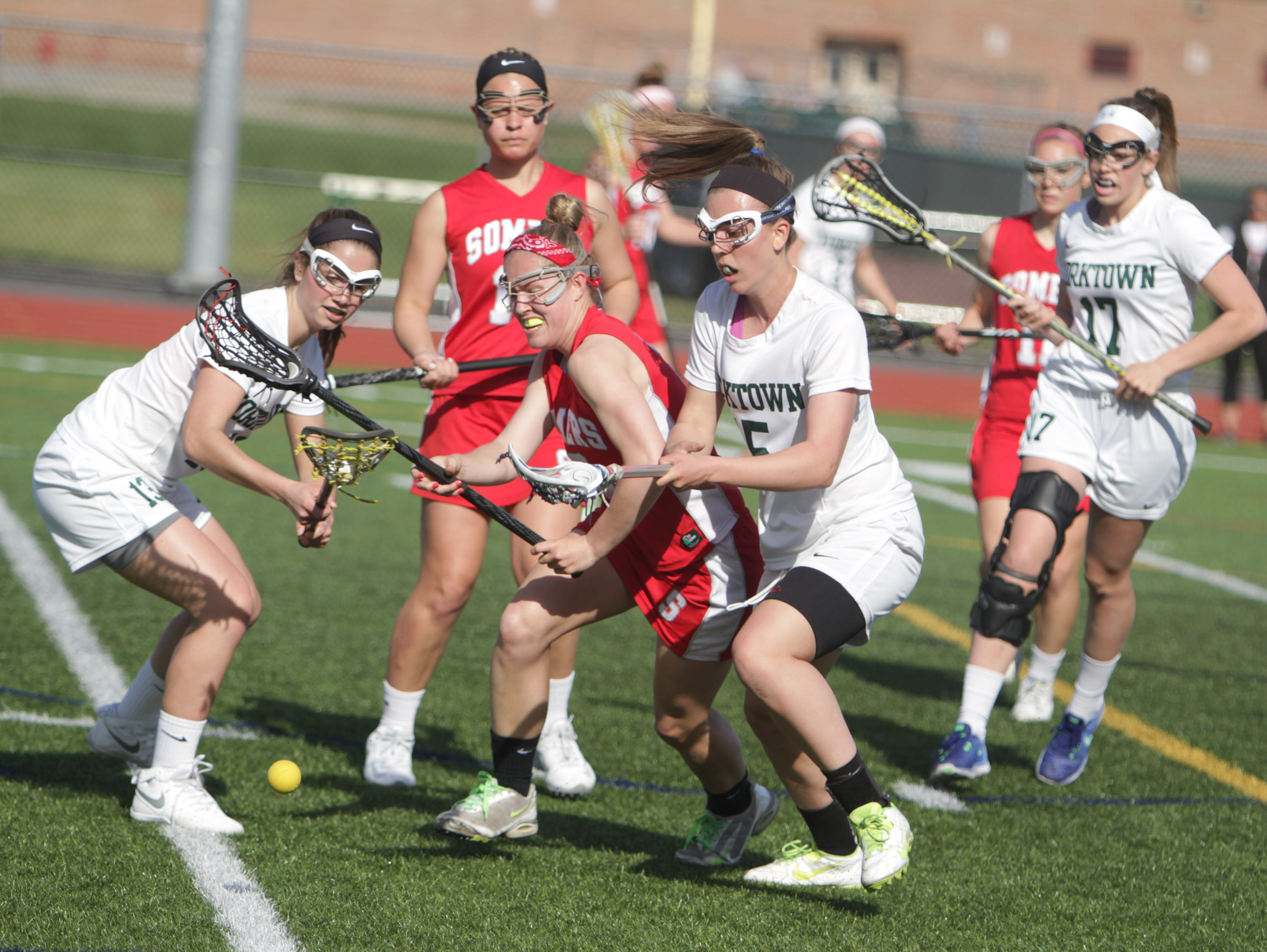 Somers' Gabby Rosenzweig (middle) and Yorktown's Rilea Fusco (left) and Ashley Stilo (right) go for a ground ball during a Section 1 girls lacrosse game between Yorktown and Somers at Yorktown High School on Thursday, April 21st, 2016. Somers won 11-10.