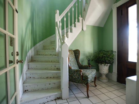 The entryway and front staircase inside the 6,000 square foot colonial revival Dave and Brittany Rademacher of Grand Ledge are renovating.  The home was built in 1873.
