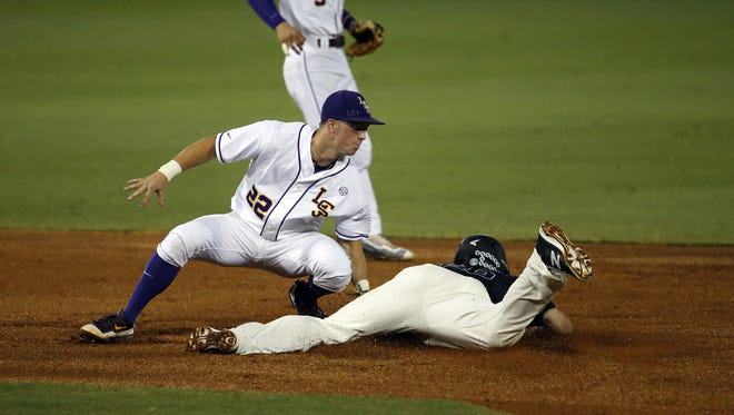 LSU infielder Cole Freeman (22) catches Coastal Carolina's Seth Lancaster stealing second in the first inning of a Super Regional NCAA college baseball game at in Baton Rouge, La., Saturday, June 11, 2016. (AP Photo/Gerald Herbert)