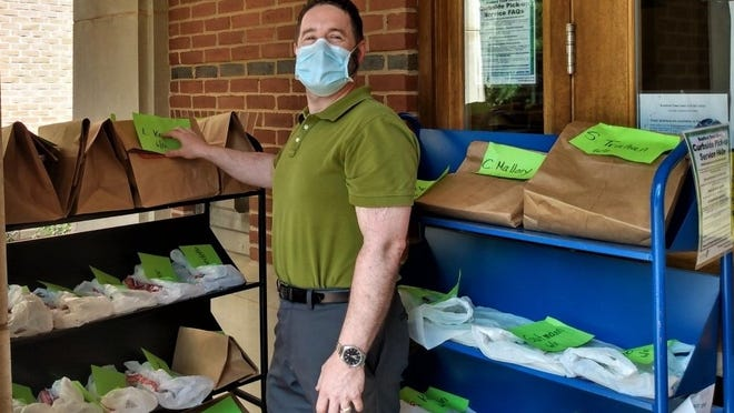 """Boxford Library Director Kevin Bourque stands by the """"curbside pickup"""" carts. The service, launched on June 8, enables patrons to oder items and then pick them up on the carts in front of the library at 7A Spofford Road."""